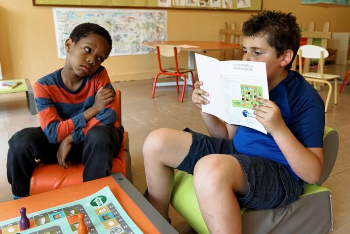 enfant lisant les règles du jeu concernant le jeu de l'oie.